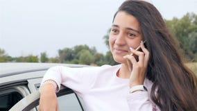 Schönes Mädchen, das am Telefon nahe dem Auto spricht Nahaufnahme stock video footage