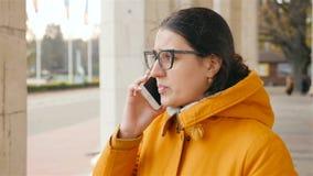 Schönes Mädchen, das am Telefon spricht Umkippengesicht Nahaufnahme Langsame Bewegung stock video