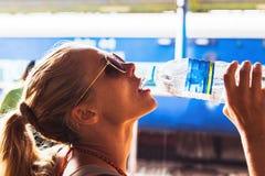 Schönes Mädchen, das Trinkwasser des Spaßes draußen, Nahaufnahmehafen hat lizenzfreies stockfoto