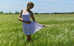 Schönes Mädchen, das unter den grünen Feldern steht Lizenzfreie Stockfotografie