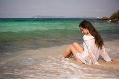 Schönes Mädchen, das in Wellen auf dem Strand sitzt Stockfotos