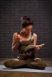 Schönes Mädchen, das Yoga-Übungen und gelesenes Buch tut Lizenzfreie Stockfotografie