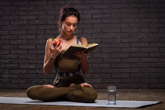 Schönes Mädchen, das Yoga-Übungen und gelesenes Buch tut Lizenzfreie Stockbilder