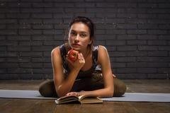 Schönes Mädchen, das Yoga-Übungen und gelesenes Buch tut Lizenzfreies Stockbild
