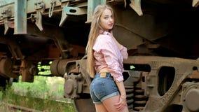 Schönes Mädchen, das zwischen Eisenbahn aufwirft Lizenzfreie Stockfotos