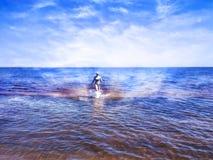 Schönes Mädchen, das zwischen glänzendes Wasser von blauem Meer geht stockbild