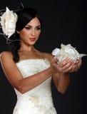 Schönes Mädchen in den Blumenblättern einer Hochzeitskleid-Holding Lizenzfreies Stockfoto