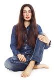 Schönes Mädchen in den Jeans, die über weißem Hintergrund sitzen stockfoto