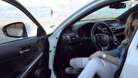 Schönes Mädchen in den Jeans klettert aus dem Auto, zufällige Art heraus stock footage