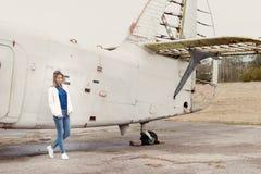 Schönes Mädchen in den Jeans und eine weiße Jacke, die nahe einem alten Flugzeug an einem bewölkten Tag steht Lizenzfreie Stockfotos