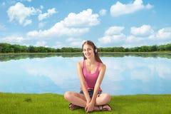 Schönes Mädchen in den Kopfhörern hört Musik nahe Fluss Stockfoto
