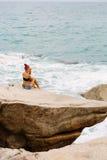 Schönes Mädchen in den kurzen kurzen Hosen sitzen auf großen Steinen Lizenzfreie Stockbilder