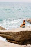 Schönes Mädchen in den kurzen kurzen Hosen sitzen auf großen Steinen Stockbilder