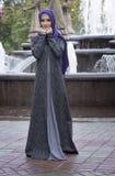 Schönes Mädchen in den modernen Moslems kleiden auf einem Hintergrund eines Brunnens an stockbild