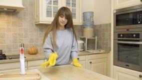 Schönes Mädchen in den Schutzhandschuhen säubern Tabelle an der Küche mit Reinigungsmittel stock footage