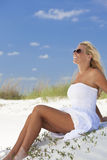 Schönes Mädchen in den weißen Kleid-Sonnenbrillen am Strand Stockfotos