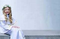 Schönes Mädchen der Erstkommunion auf dem weißen Hintergrund lizenzfreie stockbilder