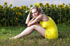 Schönes Mädchen in der gelben Kleidung sitzt Stockfoto