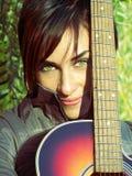 schönes Mädchen der grünen Augen und ihre Gitarre Lizenzfreie Stockfotografie