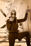 Schönes Mädchen in der Jacke, die nahe bei Kriegsflugzeugen steht. Lizenzfreie Stockbilder