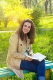 Schönes Mädchen der jungen Frau, das ein Buch lesend lächelt Stockbilder