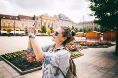 Schönes Mädchen der jungen Frau, das fotografierenden Anblick auf einem intelligenten tut stockfoto