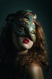 Schönes Mädchen in der Karnevalsmaske mit dem langen gelockten Haar. Maskerade-Feiertage stockfotos