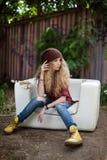 Schönes Mädchen in der modernen Kleidung auf einer defekten Couch stockfotografie