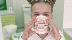 Schönes Mädchen der Nahaufnahme in einem weißen Kleid Sie hält vor einem Modellkiefer mit den Zähnen und einem netten Lächeln Sie stock footage