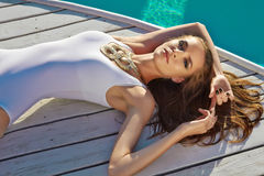 Schönes Mädchen in der perfekten Sonnenbräunehaut des in guter Verfassung nahe Swimmingpool Stockfotos