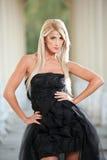 Schönes Mädchen in der schwarzen Kleideraufstellung im Freien Lizenzfreie Stockfotografie