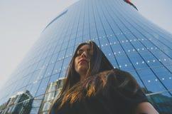 Schönes Mädchen in der schwarzen Kleidernahaufnahme auf dem Hintergrund des Geschäftszentrums Lizenzfreie Stockfotografie