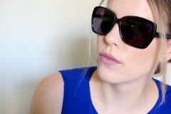 Schönes Mädchen in der schwarzen Sonnenbrille auf einem hellen Hintergrund stockfoto