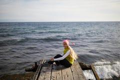 Schönes Mädchen in der Seeart, die auf Holzbrücke sitzt Reise und Ferien Getrennt auf Schwarzem Sinnliches blondes schönes Stockfoto