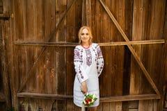Schönes Mädchen in der ukrainischen Artstellung mit Blumenstrauß auf dem Hintergrund einer hölzernen Wand lizenzfreies stockbild