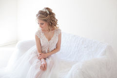 Schönes Mädchen in der Wäsche, die auf einer weißen Couchhochzeit sitzt Stockfotos