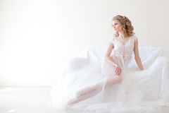 Schönes Mädchen in der Wäsche, die auf einer weißen Couchhochzeit sitzt Stockbild