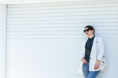 Schönes Mädchen in der weißen Jacke und in den Jeans am weißen Garagentor-Wand-Hintergrund Modischer zufälliger Mode-Ausstattungs stockbilder