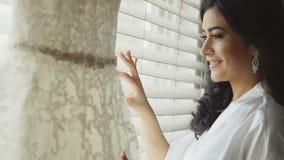 Schönes Mädchen des Brunette im weißen Hausmantel, der nahe auf dem dem Fenster ihr Hochzeitskleid hängend steht stock footage