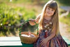 Schönes Mädchen des netten Landwirts in den Jeans Sommertag im Dorfleben mit Blumen genießend happyly lächelnd mit Kaninchenhäsch Lizenzfreie Stockfotografie