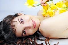 Schönes Mädchen des Porträts mit dem langen Haar mit Narzisse stockbild