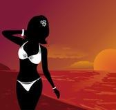 Schönes Mädchen des Schattenbildes am Sonnenuntergang auf Strand Stockfoto