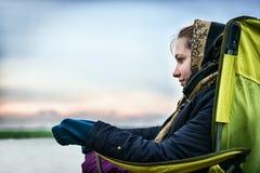 Schönes Mädchen draußen auf einem Fischenstuhl, der weg schaut Lizenzfreie Stockfotos
