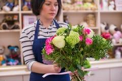 Schönes Mädchen, ein Florist, einen Blumenstrauß von Blumen auswählend Stockfotografie