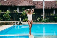 Schönes Mädchen in einem Bikini ein Sonnenbad nehmend nahe einem Pool mit blauem Wasser Sexy Modell mit einer Sportzahl steht sti Stockfotografie