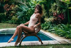 Schönes Mädchen in einem Bikini ein Sonnenbad nehmend nahe einem Pool mit blauem Wasser Sexy Modell mit einer Sportzahl steht sti Lizenzfreie Stockfotografie