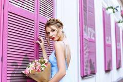 Schönes Mädchen in einem blauen Kleid, das auf der Straße nahe einem Café mit rosa Fenstern aufwirft Stockfotos