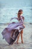 Schönes Mädchen in einem feenhaften purpurroten langen Kleid auf einer Küste stockfotografie