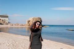 Schönes Mädchen in einem gekleideten Hut und in den Gläsern geht entlang den Strand und ist glücklich Stockfoto