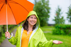 Schönes Mädchen in einem grünen Regenmantel und mit einem Regenschirm Stockfoto